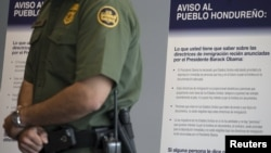 A U.S. Customs and Border Protection officer stands in front of a Spanish-language poster being used in a campaign to discourage illegal border crossings into the United States during a news conference at the Ysidro border crossing in San Ysidro, California, Aug. 18, 2015.