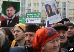 People hold banners of Vladimir Putin and Ramzan Kadyrov, as they take part in a rally marking the 13th anniversary of the adoption of the Constitution of Russian region of Chechnya, in the regional capital of Grozny, Russia on March 23, 2016.