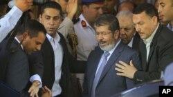 Nhân viên bảo vệ an ninh vây quanh Tổng thống tân cử Ai Cập Mohammed Morsi khi ông rời một đền thờ Hồi giáo ở Cairo sau lễ cầu nguyện ngày thứ Sáu