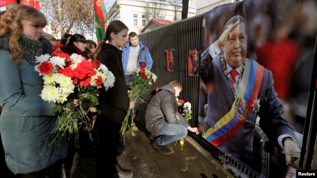 People bring flowers to the Venezuelan embassy to pay tribute to the late Venezuelan President Hugo Chavez, in Minsk, March 6, 2013.