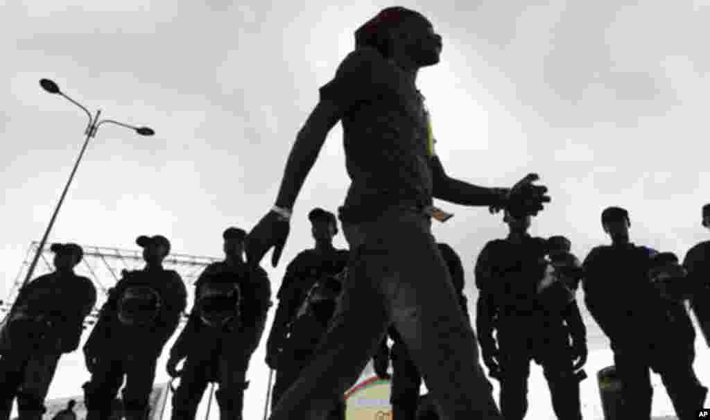 """An Equatorial Guinea fan walks past Equatorial Guinea's police special forces standing at their positions at Estadio de Bata """"Bata Stadium"""", which will host the opening match and ceremony for the African Nations Cup, in Bata January 21, 2012."""