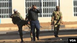 FILE: A soldier assaults a man on the streets of Harare following demonstrations by opposition party supporters.