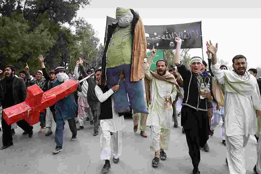 Para demonstran meneriakkan slogan-slogan anti-AS sambil menggotong orang-orangan Presiden Obama pada sebuah aksi protes di Jalalabad (AP).