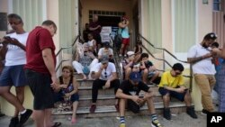 People congregate at a wifi hotspot in the aftermath of Hurricane Maria with many cellphone towers down in San Juan, Puerto Rico, Sept. 24, 2017.