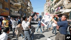 A protester uses a shoe to beat a picture of Syria's President Bashar al-Assad during a protest organized by Lebanese and Syrians living in Lebanon, in solidarity with Syria's anti-government protesters, in the port-city of Tripoli, northern Lebanon, Octo