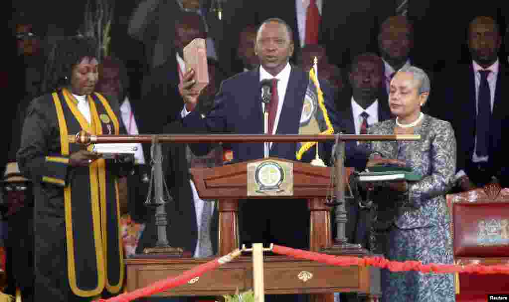 Kenya's President Uhuru Kenyatta takes the oath of office as his wife Margaret holds a bible during the official swearing-in ceremony at Kasarani Stadium in Nairobi, April 9, 2013.
