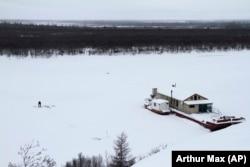 Seorang nelayan mengangkut tangkapannya dari lubang di es dekat tongkang penelitian Stasiun Sains Timur Laut dekat Chersky, Rusia. (Foto: AP/Arthur Max)