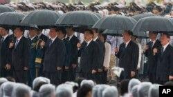 中共总书记习近平、中国总理李克强、中共政治局常委张德江、俞正声、王岐山等人在雨中在人民英雄纪念碑前唱国歌(2013年10月1日)