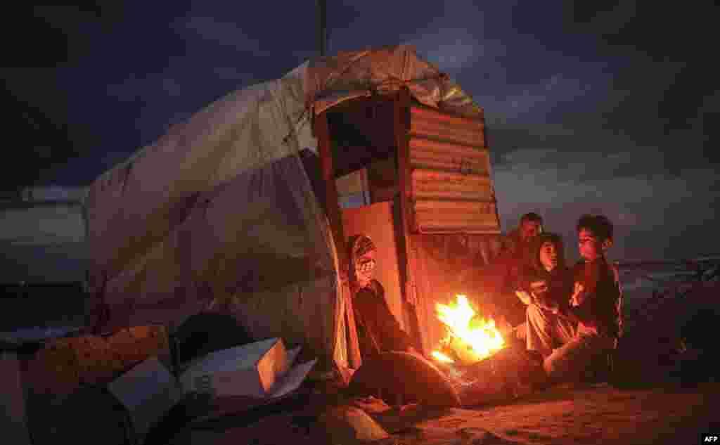 팔레스타인 가자시 해변의 판잣집에서 한 가족이 추위를 피하기 위해 모닥불 주변에 모여있다.
