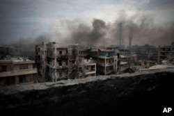 FILE - Smoke is seen rising over Saif Al Dawla district, in Aleppo, Syria.