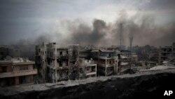 FILE - Smoke is seen rising over Saif Al Dawla district, in Aleppo, Syria.