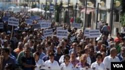 Para pekerja pada galangan kapal di kota Viana do Castelo, Portugal berjalan menuju pusat kota hari Rabu (6/7) untuk memrotes rencana PHK atas 380 pegawai, atau lebih dari separuh jumlah pegawai di tempat itu.