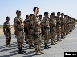 FILE - French troops stand at attention during a handover ceremony of the Timbuktu mission from France to Burkina Faso at Timbuktu airport, April 23, 2013