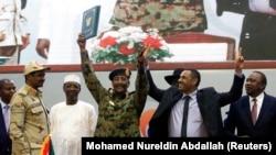 Le lieutenant-général Abdel Fattah Al-Burhan, président du Conseil militaire, et le chef de la coalition de l'opposition soudanaise Ahmad al-Rabiah célèbrent la signature de l'accord de partage du pouvoir qui ouvre la voie à un gouvernement de transition