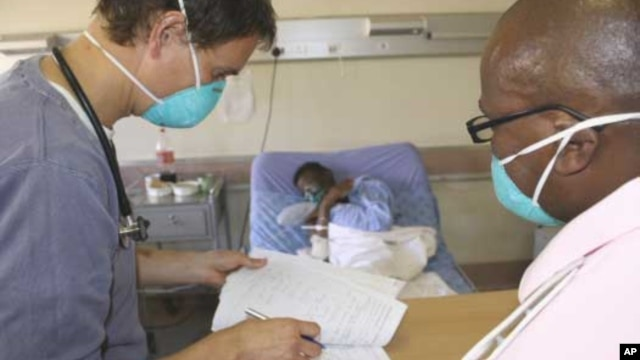 A doctor (left) and a nurse discuss the condition of a patient infected with both HIV and tuberculosis in a hospital in South Africa