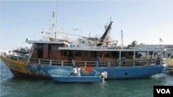 Atas undangan lembaga WWF, mahasiswa Univeristas Kristen Petra sedang mengerjakan lukisan cat pada badan Kapal Gurano Bintang di Kendari.