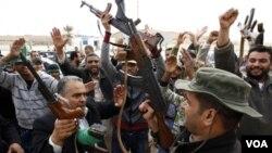Pendukung Gaddafi menyerukan slogan merayakan perebutan kembali sebuah kantor polisi di Bin Jawad, Sabtu (12/3).