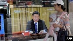2019年1月2日,台湾新北市的一位母亲带着孩子经过一台电视,屏幕上显示中国领导人习近平就台湾问题发表讲话。