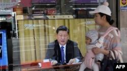 2019年1月2日,台灣新北市,一位母親帶著孩子經過一台電視,上面顯示中國領導人習近平就台灣問題發表講話。