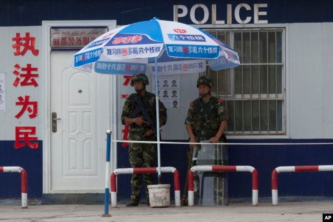 FILE - Chinese paramilitary police stand on duty in front of a wanted poster in the city of Aksu in western China's Xinjiang province, July 17, 2014. China has blanketed parts of Xinjiang, home to Muslim, Turkic-speaking Uighurs, with heavy security.