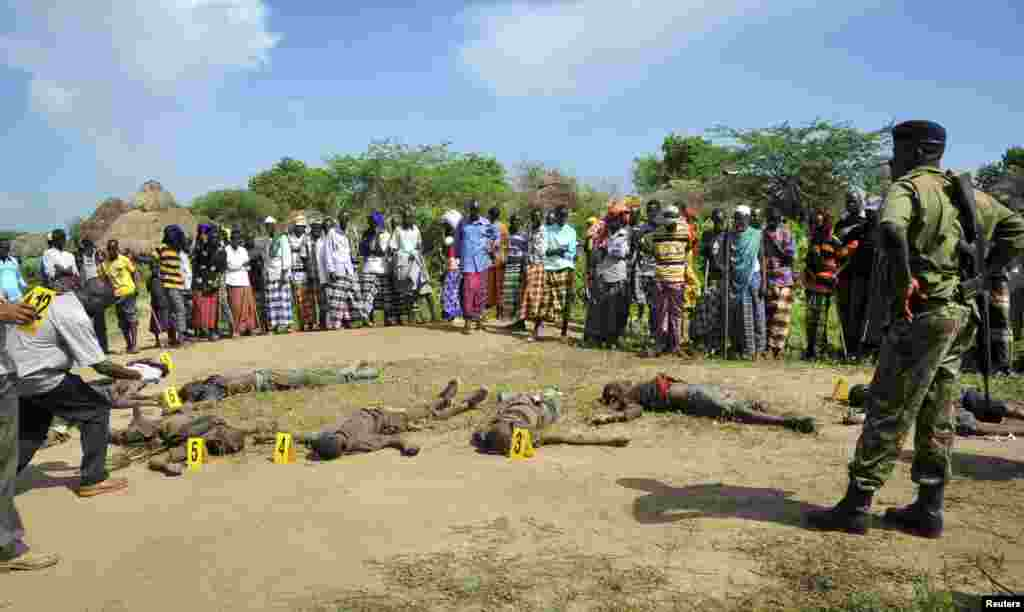 Villagers and police view the bodies of suspected attackers from the Pokomo tribe, following tribal clashes in Kipao village in the Tana River Delta region of southeastern Kenya Dec. 21, 2012.