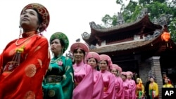 "Vietnamese women wearing ""ao dai"" line up during Lang Pagoda Festival in Hanoi, Vietnam. Lang Pagoda was built in the 12th century during the Ly Dynasty. (AP Photo/Chitose Suzuki)"