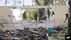 索马里军人观察青年党的汽车炸弹的残骸(2015年4月14日)