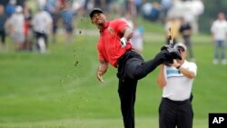 FILE - Tiger Woods makes an awkward follow through after hitting from the lip of a fairway bunker on the second hole during the final round of the Bridgestone Invitational golf tournament Sunday, Aug. 3, 2014.
