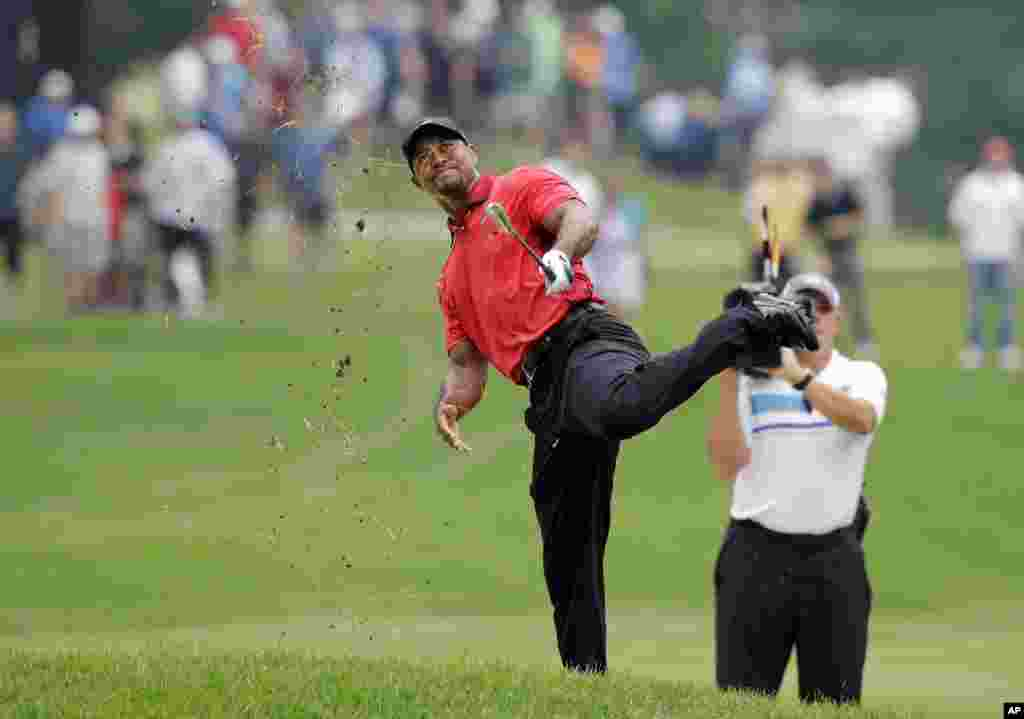 Tiger Woods makes an awkward follow through after hitting from the lip of a fairway bunker on the second hole during the final round of the Bridgestone Invitational golf tournament at Firestone Country Club in Akron, Ohio, USA.