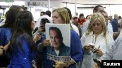 Una mujer sostiene una foto de Manuel Rosales junto a la esposa de Rosales, Eveling Trejo de Rosales, mientras aguardaban su llegada al aeropuerto de Maracaibo, Venezuela, el jueves 15 de octubre de 2015.