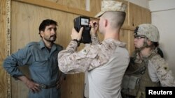U.S. marines of Fox Co, 2nd Battalion, 7th Marines Regiment get a biometric scan of an Afghan local police trainee before the start of a basic police course training at Combat Outpost Musa Qal-Ah in Helmand province, October 31, 2012.