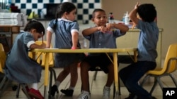 In this Oct. 13, 2017 file photo, children discuss their thoughts about Hurricane Maria at Ramon Marin Sola Elementary School in Guaynabo, Puerto Rico. (AP Photo/Carlos Giusti, File)