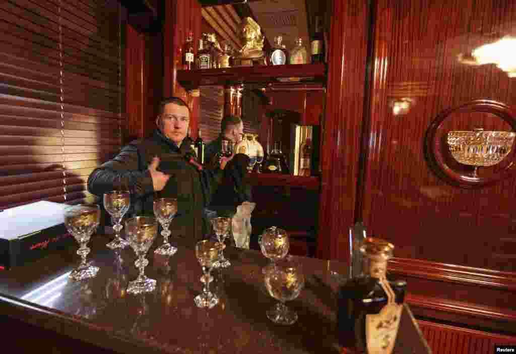 A man gestures behind the interior bar of the Mezhyhirya residence of Viktor Yanukovich in the village Novi Petrivtsi, Feb. 22, 2014.