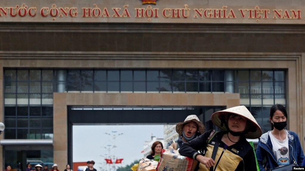 Phụ nữ Trung Quốc mang vác hàng hóa từ cửa khẩu Móng Cái sang Trung Quốc.