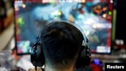 资料照:一名男子在北京的一家网吧玩电游。(2021年8月31日)