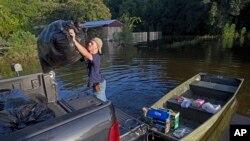 路易斯安那州的一位青年把朋友的被水淹了的家中的东西装上船(2016年8月20日)
