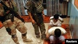 Binh sĩ Iraq canh gác các nghi can chiến binh al-Qaida bị bắt trong một cuộc đột kích ở Baquba.