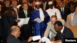 Le président soudanais Omar Hassan al-Bashir, à gauche en bas, et le président tchadien Idriss Deby, à droite, signent un accord de paix sous le regard du secrétaire général des Nations unies Ban Ki-moon (en haut) et du président sénégalais Abdoulaye Wade, centre, 13 mars 2008.