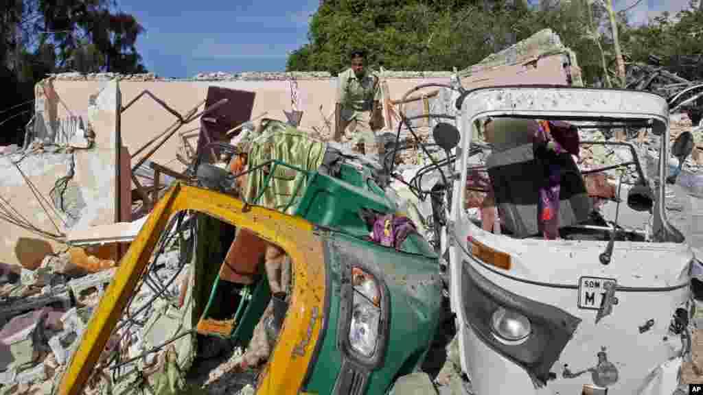 Un agent des forces de sécurité de la Somalie devant des véhicules calcinés à Mogadiscio, en Somalie, le 15 juin 2017.