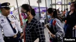 2020年2月18日,戴著口罩的菲律賓勞工在馬尼拉國際機場準備登機出國。