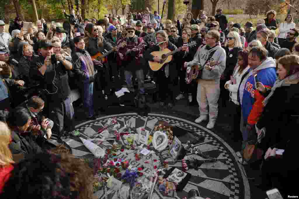 Fans of former Beatle John Lennon gather at the Imagine mosaic in the Strawberry Fields section of New York's Central Park to mark the 35th anniversary of his death, in New York, Dec. 8, 2015.