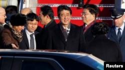 日本首相安倍晉三(中)到達華盛頓附近的安德魯斯空軍基地時受到美國首席禮賓官馬歇爾(左)的歡迎
