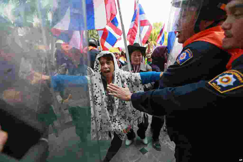 Riot police officers try to stop anti-government protesters from storming an office building during a rally at the Department of Special Investigation on the outskirts of Bangkok, Dec. 23, 2013.