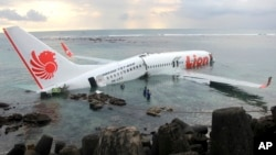In this photo released by Indonesian police, the wreckage of a crashed Lion Air plane sits on the water near the airport in Bali, Indonesia, April 13, 2013.