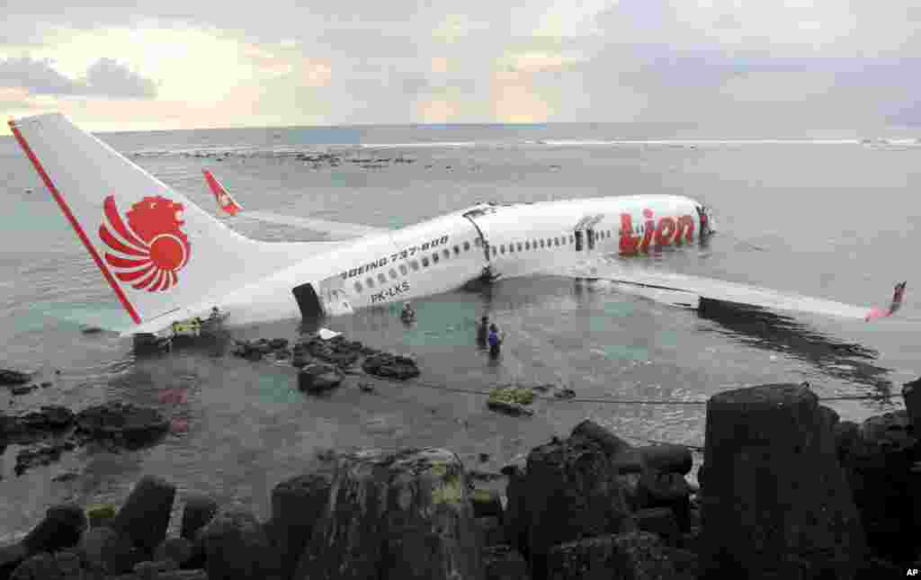 In this photo released by Indonesian Police, the wreckage of a crashed Lion Air plane sits on the water near the airport in Bali, Indonesia. The plane carrying more than 100 passengers and crew overshot a runway on the resort island of Bali and crashed into the sea, injuring nearly two dozen people, officials said.