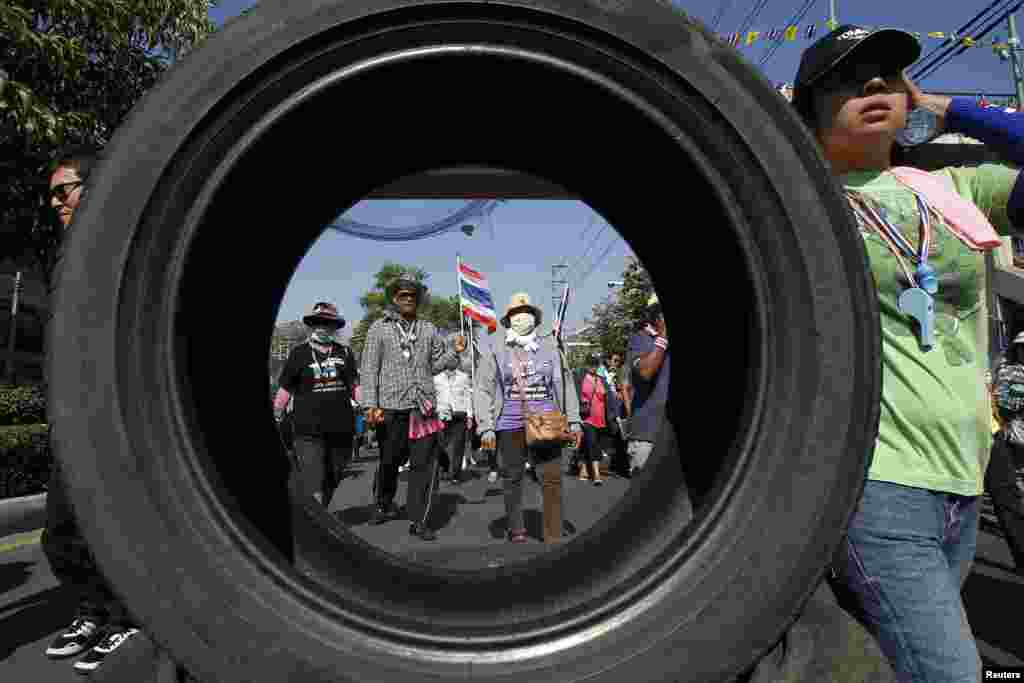 Anti-government protesters march past one of their roadblocks made of tires in central Bangkok, Thailand.