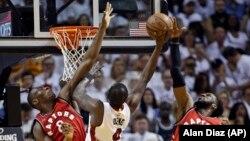 Luol Deng N.9 de Miami Heat mène une attaque sous le panneau face à Bismack Biyombo N.8 et DeMarre Carroll N.5 des Raptors de Toronto qui défendent pour leur équipe lors du match 6 des demi-finales de la Conférence Est de la NBA de basket-ball, 13 mai 2016, à Miami.