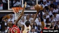 Luol Deng du Miami Heat (9) contre Bismack Biyombo des Toronto Raptors (8) et DeMarre Carroll (5) , le 13 mai 2016 à Miami.