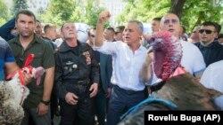 Владімір Плахотнюк на акції протесту 9 червня 2019 року. Протестувальники тримають індиків і кидають їх за огорожу служби президента Молдови