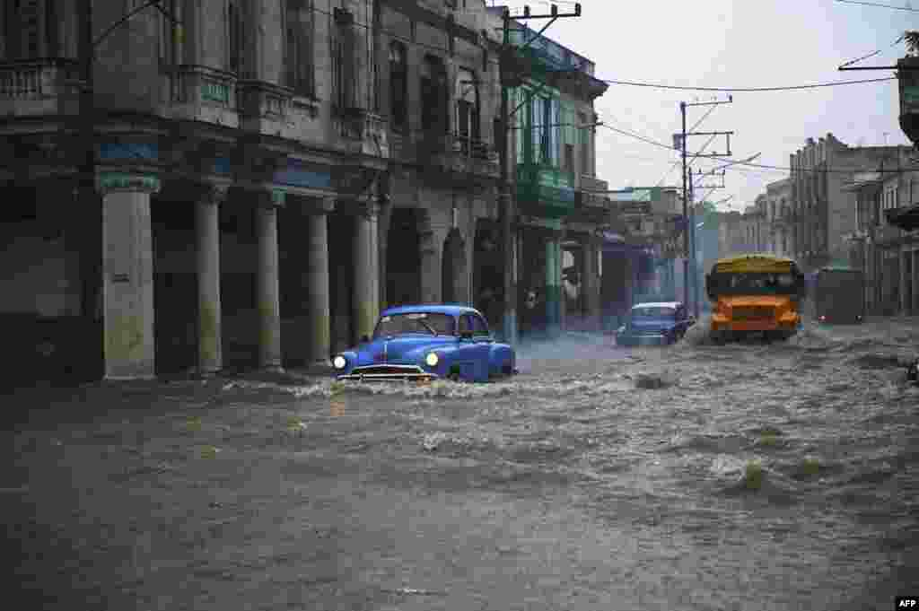 Old American cars and buses drive through a flooded street in Havana, Cuba, June 30, 2021.